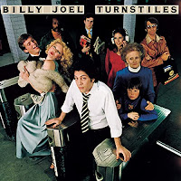 Camera looks down on Billy Joel standing in a turnstile at a station with an assortment of people (dancers, office workers etc) behind him