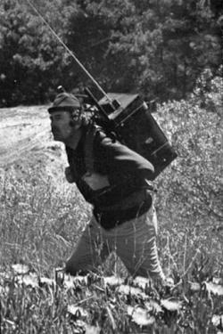 hombre portando un primer dispositivo de registro ECG con un transmisor en una mochila por un prado