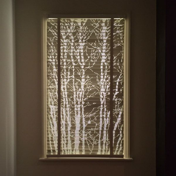 framed pierced hole tree design on Venetian blind allows light to shine through