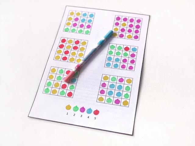 na zdjęciu łamigłówka z sześcioma tabelkami z kolorowymi bombkami zastępującymi liczby
