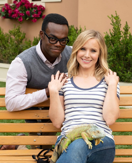 image of actors William Jackson Harper and Kristen Bell in character as Chidi and Eleanor; Bell has a big iguana sitting on her lap