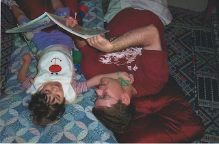 Father reading a book to daughter with significant disabilities while lying on the floor.