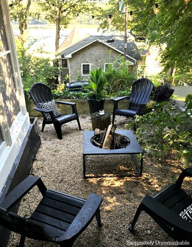 Black Adirondack chairs with white and black pillows  around a fire pit on a gravel patio