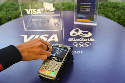 Visa logo on table with credit card reader and persons hand wearing payment ring being scanned by machine