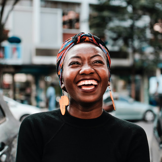 Laughing woman with headscarf and oversized earrings.