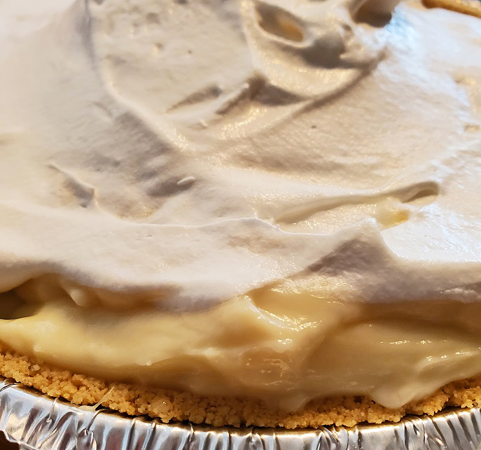 a graham cracker crust banana cream pie with whipped cream on top