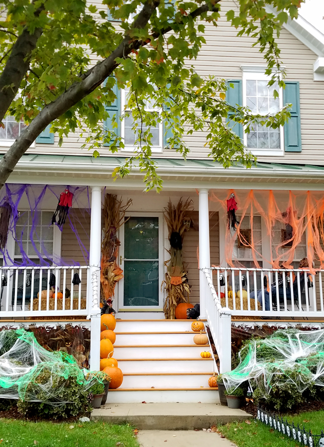 front porch decorated for Halloween with pumpkins and spooky items