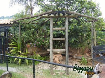 Banco de pedra no jardim, com pedra moledo, com a mesa de pedra e o pergolado de madeira.