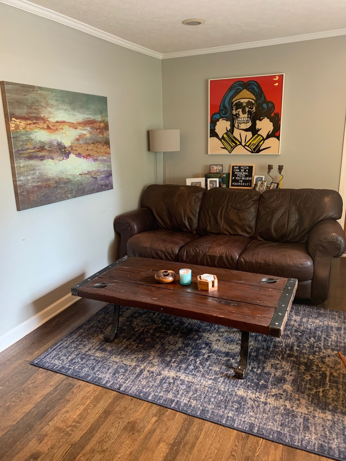 a living room with an abstract painting and a painting of wonder woman