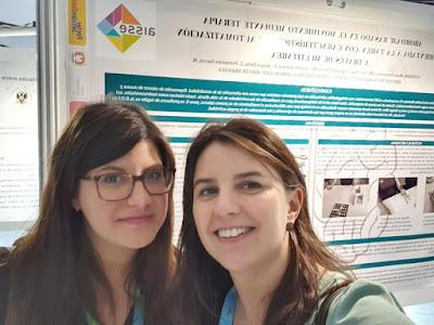 Ana e Inma con el póster en la sección de Neuroterapia ocupacional