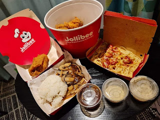 A shot of a red cylindrical bucket containing light golden brown pieces of Chicken next to three rectangular boxes that are red with Jollibee in white font with an animated bee on them containing golden brown pieces of food on a bright background