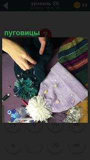 Женщина пришивает пуговицы, тем самым украшая детские шапочки