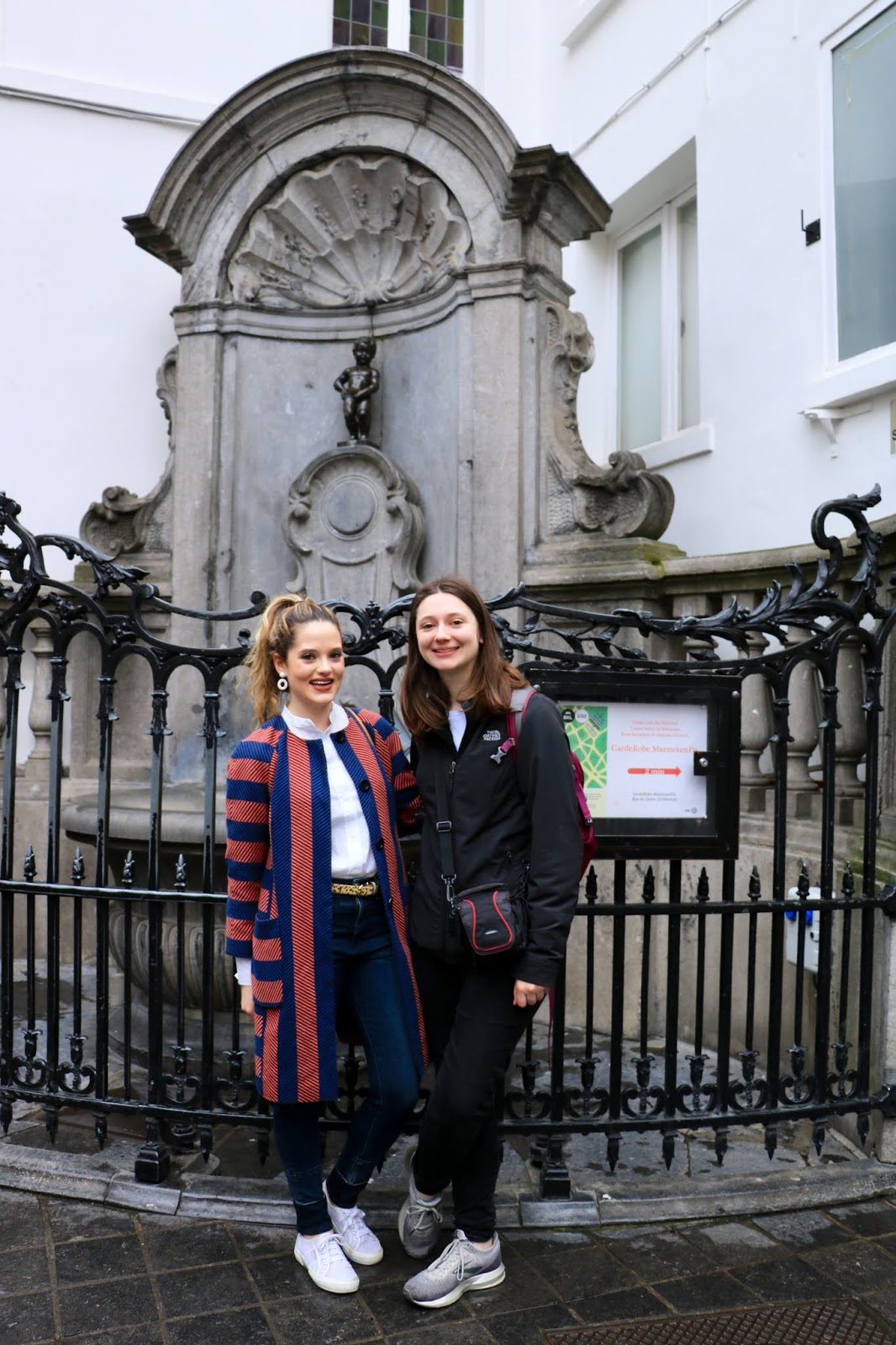 Fashion blogger Kathleen Harper posing in front of the Manneken Pis with her sister in Brussels, Belgium