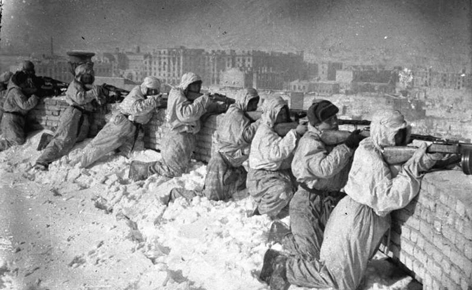 Soviet soldiers in camouflage winter uniforms line up along the roof of a house in Stalingrad, in January of 1943.