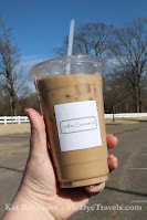 A clear plastic cup of iced coffee with cream from Coffee Central held in hand at Snowden Grove Park in Southaven, MS.