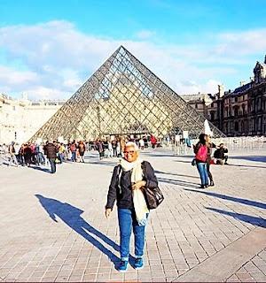idosa em frente a uma piramide de vidro
