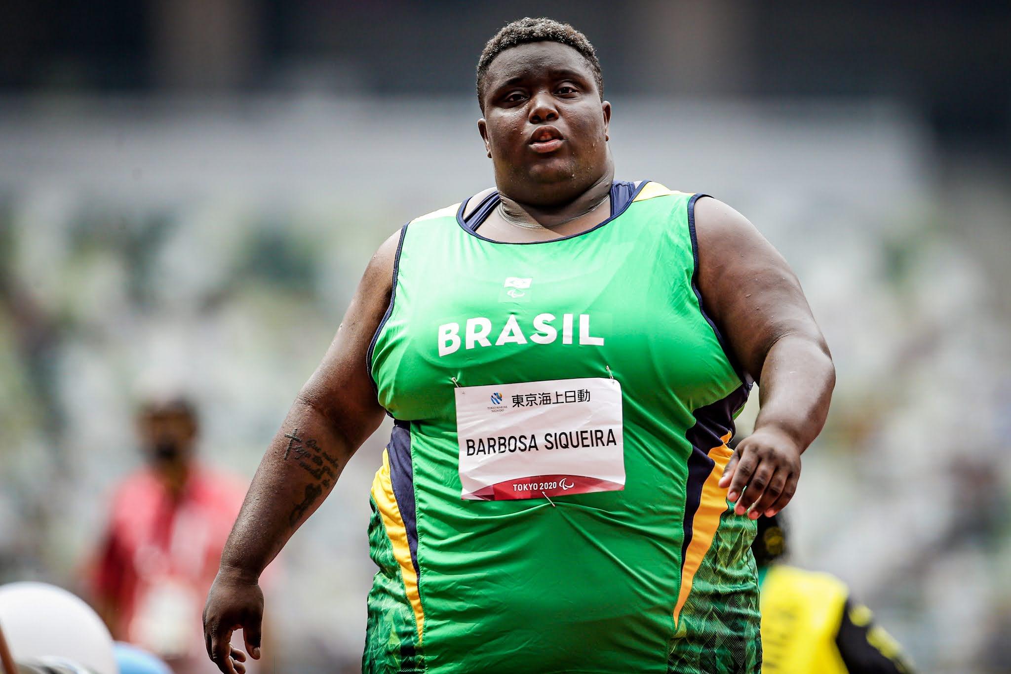 Tuany Priscila, negra e cabelo curto, veste verde, o uniforme do time brasileiro de atletismo