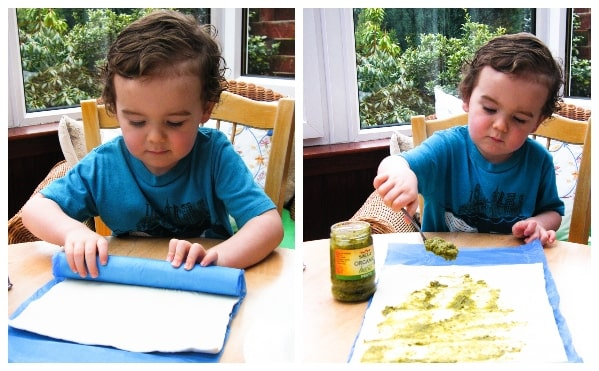 Making vegan pesto cheese swirls - Step 1 - Boy spreading pesto on a sheet of puff pastry