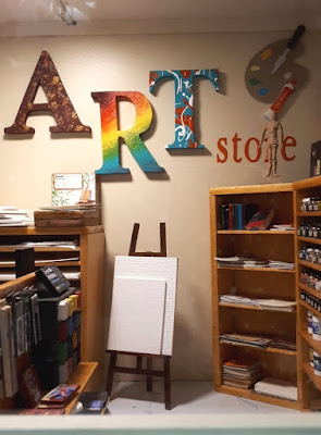 One-twelfth scale modern miniature art store displaying various paints, mark-making material, books and supports.