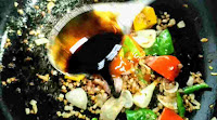 Pouring soya sauce in stir fried vegetables and herbs for chilli chicken gravy