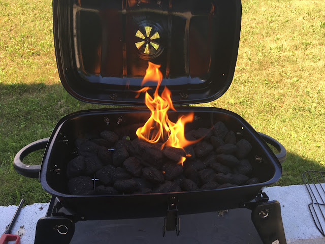 The charcoal lit in the grill.