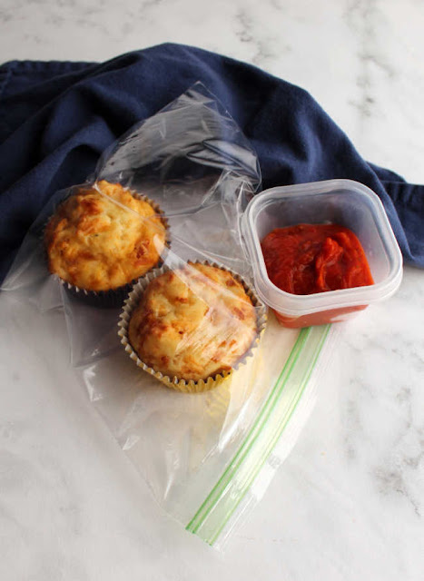 two muffins in plastic bag with small container of pizza sauce