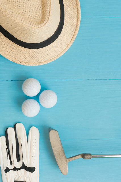 A golf hat, club, balls and gloves
