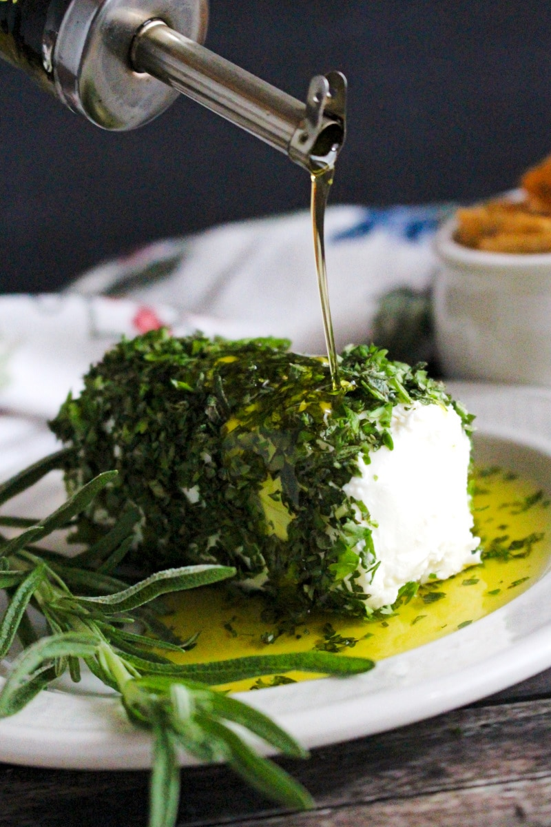 Side view of Herb and Olive Oil Goat Cheese Log on a cream colored plate with olive oil being poured onto it.