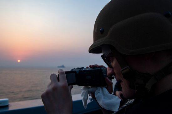 Un membro della squadra SNOOPIE di un cacciatorpediniere con una videocamera in mano.
