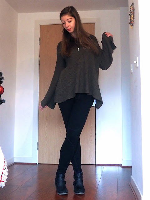 Oversized - outfit of large, loose green jumper, black t-shirt, black seam detailed leggings, and black heeled ankle boots