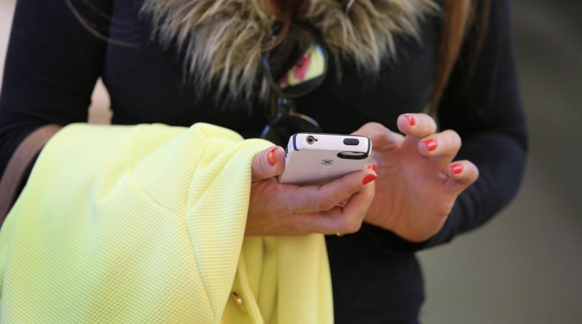 Multe ai pedoni che attraversano la strada guardando il cellulare o ascoltando musica con le cuffie