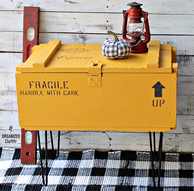 A hinged crate is painted and stenciled with metal legs added for a table.