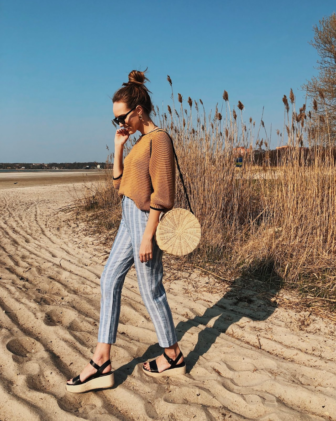 neutral minimal style summer outfit striped linen pants round rattan bag knit platform sandals