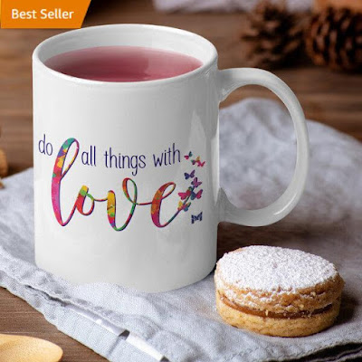 "Picture ""Do all things with love"" mug on a table next to some scones with ""Best Seller"" label in the top left."