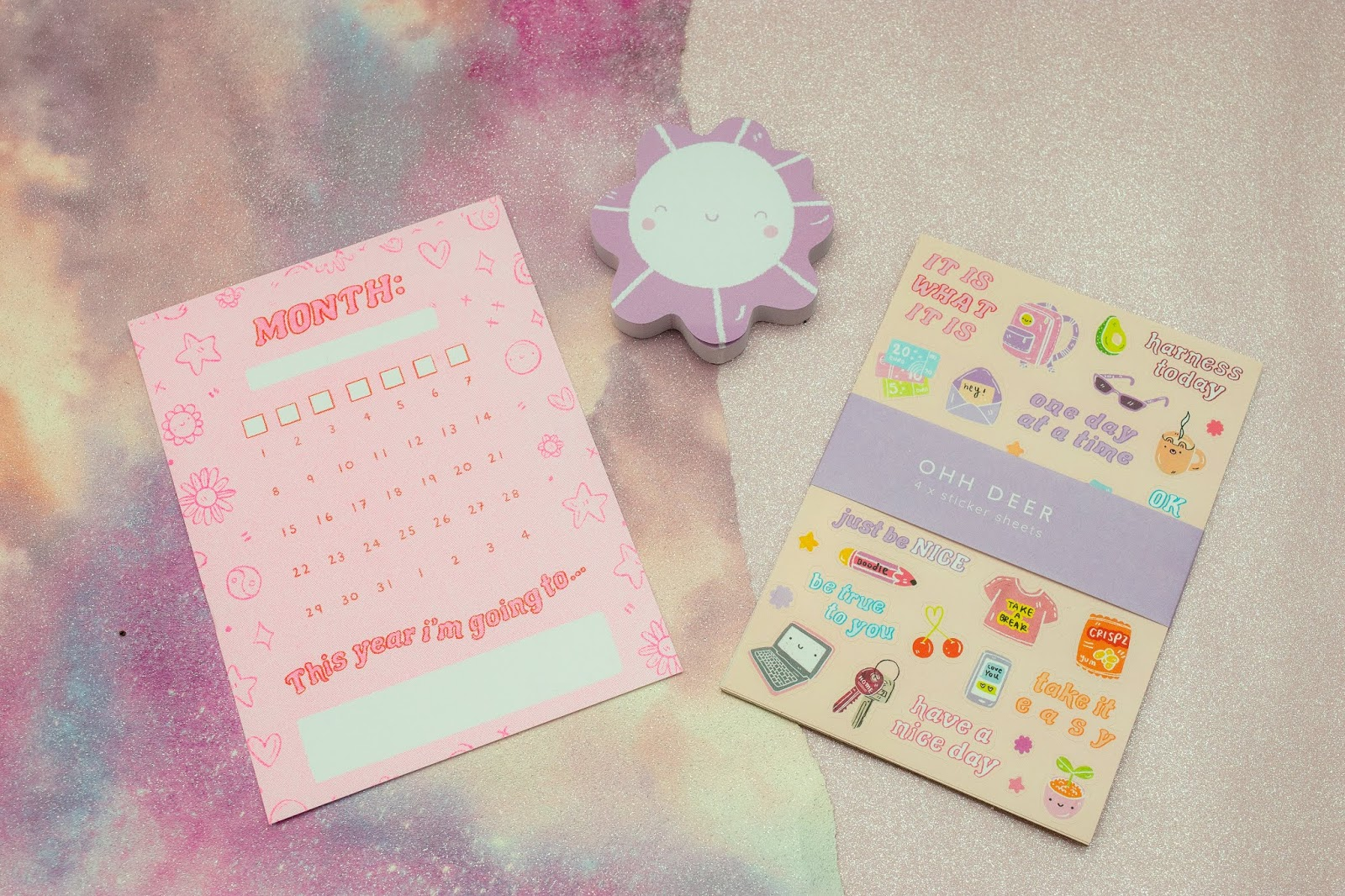A flat lay of the postcard with a calendar on, purple flower post it notes and a pack of doodle design stickers.