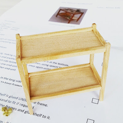 A half-finished one-twelfth scale tea trolley sitting on the instruction sheet.