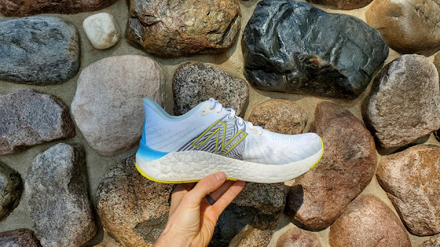 Medial view of Vongo V5 seen held out to rocks. Midsole seen heavily in the heel and slightly lowering steadily into the forefoot.