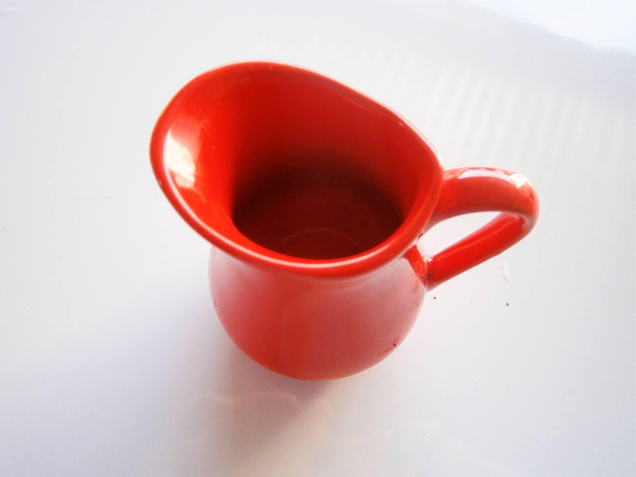 Jarra pequeña de color rojo puesto sobre un fondo de color blanco