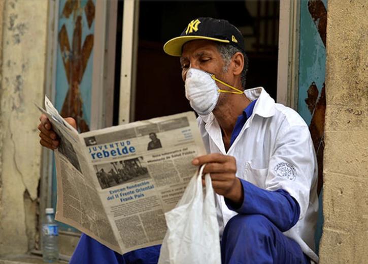 Un hombre con su barbijo lee un diario local en La Habana / AFP