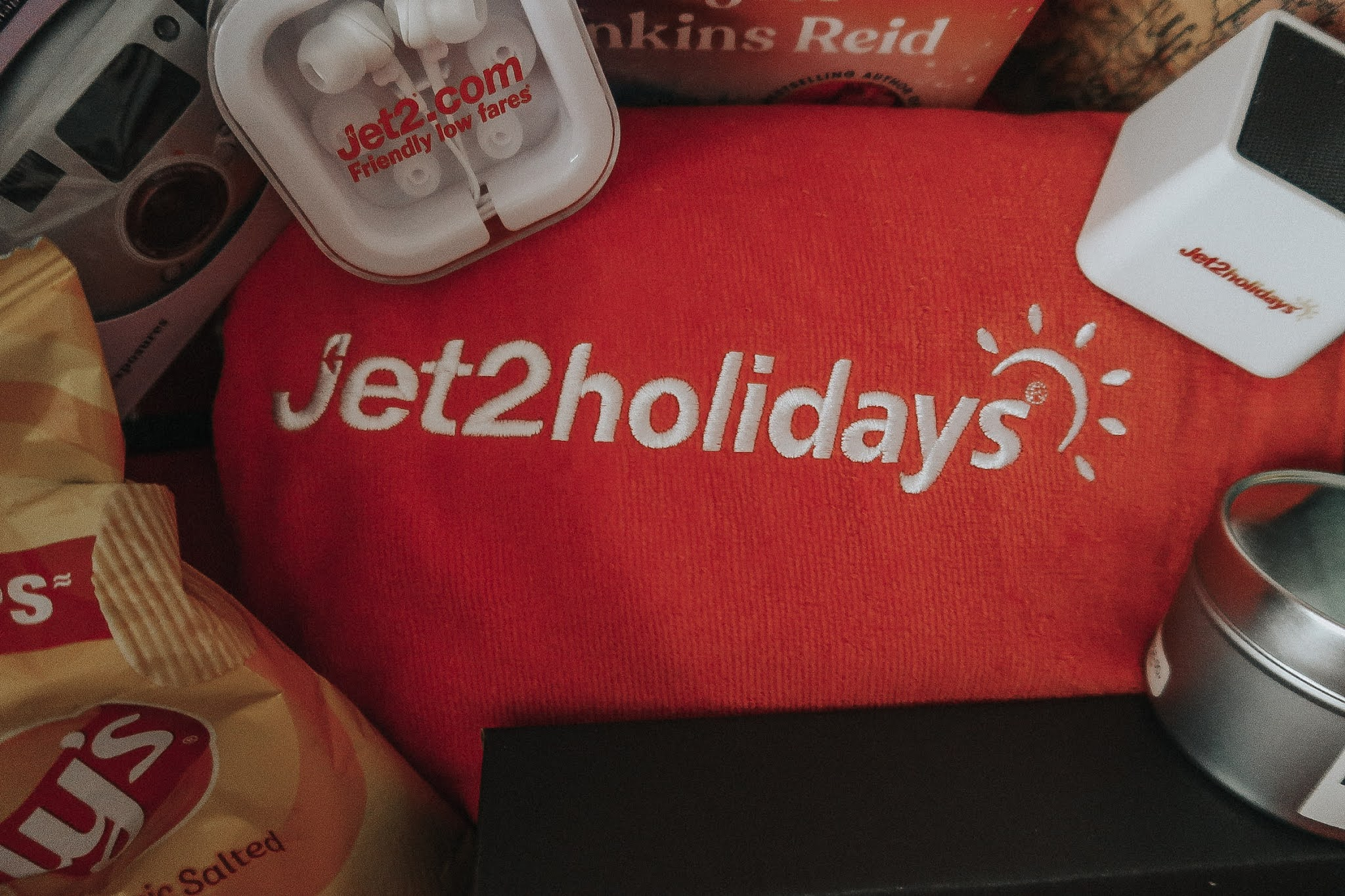 A red beach towel with Jet2 holidays in white stitching.