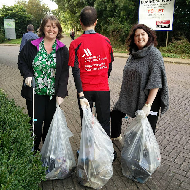 Three members of the Marriott team picking litter