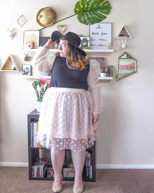 An outfit consisting of a black wide brim hat, white sheer long sleeve puffy sleeve blouse under a black mockneck dress tucked into a pastel pink skirt with a pastel pink sheer mesh overlay adorned with coordinated pink rosettes.