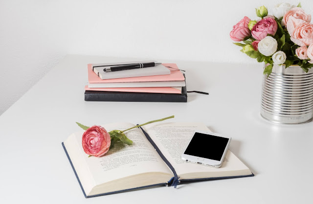 There is an open book on a white desk. There is a phone and a rose resting on the book, with a tin can filled with the rest of the roses. It's a pink bouquet. There is also a stck of notebooks in the background.