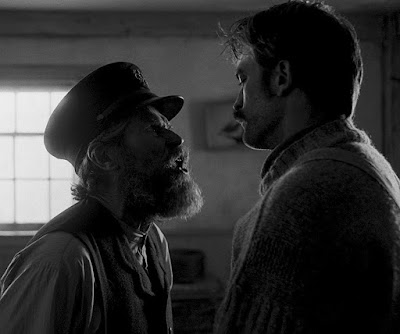 The Lighthouse 2019 movie scene showing Thomas Wake (Willem Dafoe) confronting and yelling at Ephraim Winslow (Robert Pattinson)