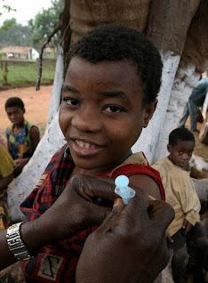 Mbuti woman of the Ituri Rainforest in equatorial Africa receives an immunization shot