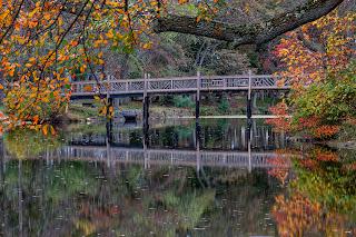 A footbridge crossing Divine Lake in Spring Lake, New Jersey during peak foliage.