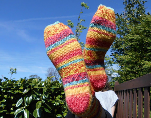 A pair of orange striped socks being modelled on feet.  The model has her feet over the end of a garden wooden bench so the socks are viewed against a blue sky