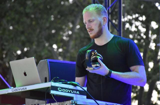 El DJ Nico DiMarco frente a un ordenador Apple en una mesa de mezclas, camiseta oscura y fondo de arboleda