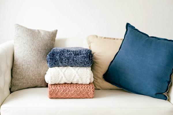 Sofá bege clean com almofadas bege e roupas dobradas