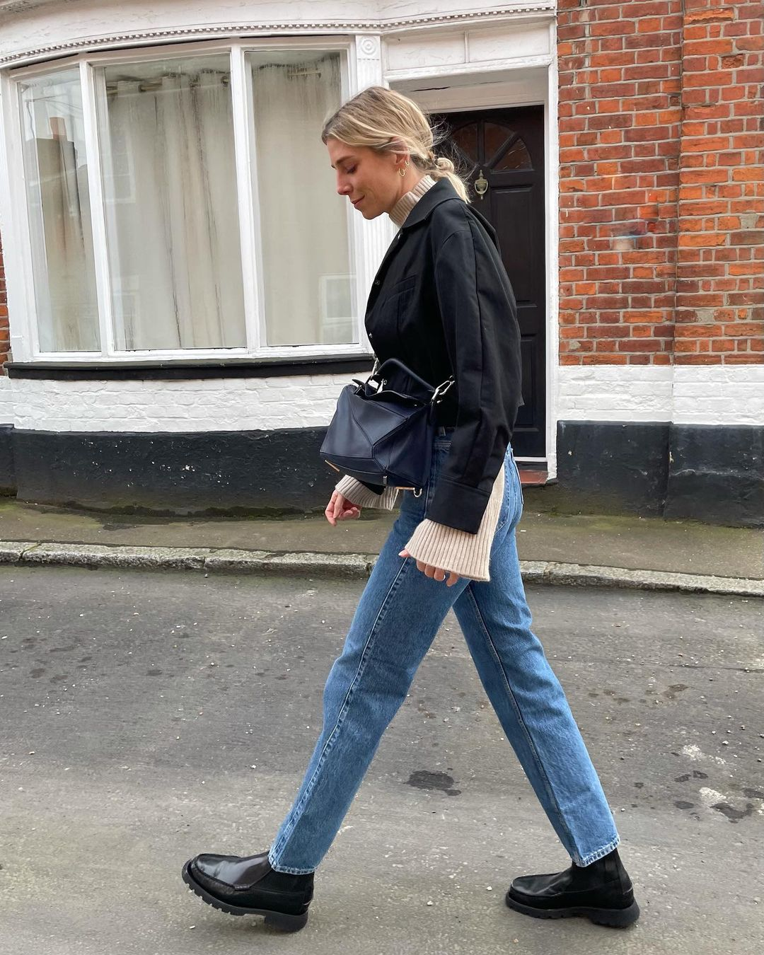 Transitional Spring Outfit Idea - Lindsey Holland Instagram Look With a Black jacket, Beige Turtleneck Sweater, Jeans, Loewe Crossbody Bag, and Lug-Sole Boots